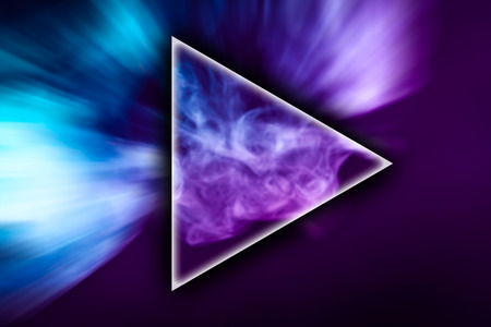 Fog colored with bright pink and blue gel in the shape of a triangle on dark background Stockfoto