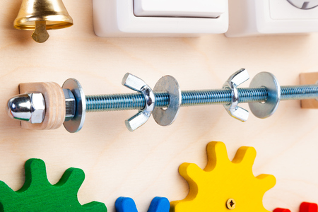 Close-up roller, screw with bolts and bell on a wooden busy board- educational toy for children, babies on a white isolated background. A toy for entertaining children and parents Reklamní fotografie