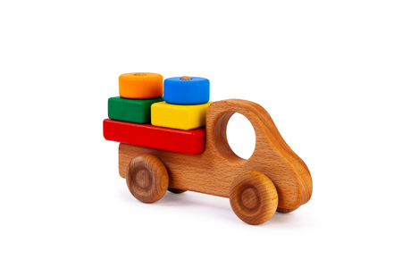 Photo of a wooden car truck loaded with small colorful wooden geometric figures: a circle, a triangle, a rectangle, a square made of beech on a white isolated background Reklamní fotografie