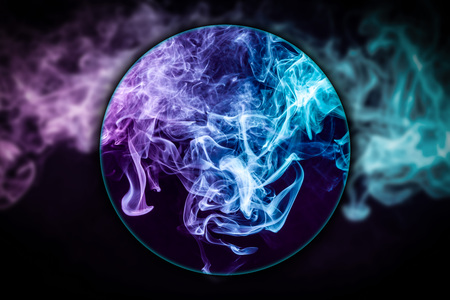 Close-up  pink and blue smoke  blown under a magnifying glass  on black background