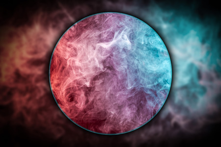 Close-up abstract art colored  red and blue smoke   blown under a magnifying glass  on black isolated background. Stop the movement of multicolored smoke on dark background