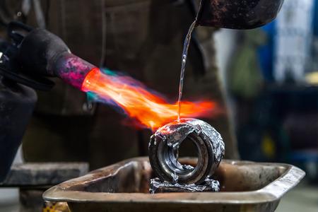 Travailleur masculin professionnel utilisant une torche à gaz pour faire fondre le métal de plomb. Gros plan sur un brûleur à gaz avec un feu visant directement le métal en fusion. Industrie du fer et de l'acier