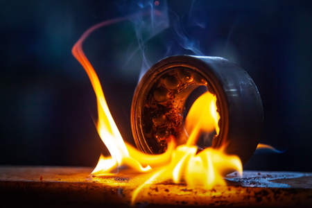 Close-up of the burning of the automotive part of the bearing using a gasoline burner in the auto repair shop. Burning flame fire on metal bearing Фото со стока