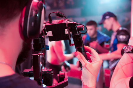 The operator shoots video at a sporting event. Professional video technician at work. Videographer for the event, rear view. The operator while working with a large professional camera.