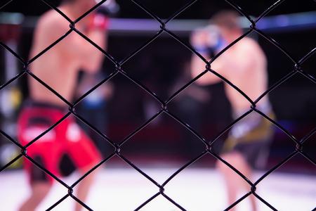 Concepto deportivo de lucha sin reglas. Dos atletas de boxeador en la arena de la escena octogonal. Estado de ánimo peleas de boxeo sin reglas de boxeo MMA. Una mirada alternativa a las peleas de boxeo a través de la jaula de metal Foto de archivo