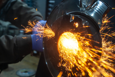 A young man welder in a blue gloves grinder  bearing metal an angle grinder   in the   workshop, sparks fly to the side