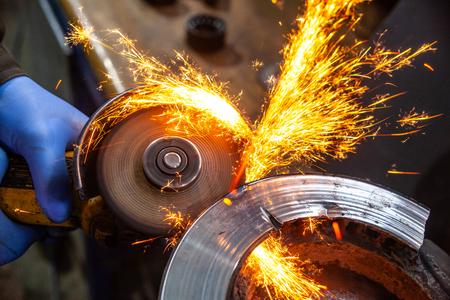 Eine Nahaufnahme eines Automechanikers mit einem Metallschleifer, um das Lager in einer Autowerkstatt zu schneiden, helle Blitze fliegen in verschiedene Richtungen. Arbeit der Automechaniker. Standard-Bild