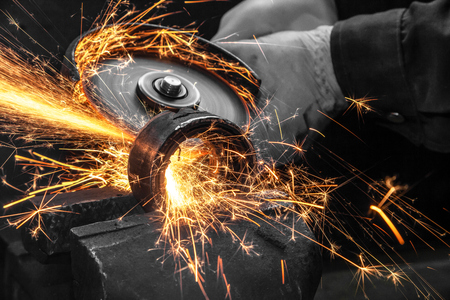 Close-up on the sides fly bright sparks from the angle grinder machine. A young male welder in a white working gloves grinds a metal product with angle grinder in the garage Imagens