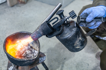 Professional male worker using a gas torch to melt lead metal. Close-up a gas burner with a fire aimed directly at the molten metal.Iron and steel industry