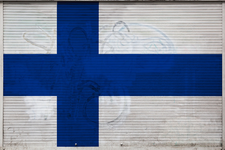 Close-up of old metal wall with national flag of Finland. Concept of Finland export-import, storage of goods and national delivery of goods. Flag in grunge style Stock Photo