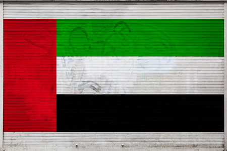 Close-up of old metal wall with national flag of United Arab Emirates. Concept of United Arab Emirates export-import, storage of goods and national delivery of goods. Flag in grunge style