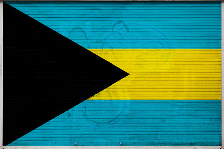 Close-up of old metal wall with national flag of Bahamas. Concept of Bahamas export-import, storage of goods and national delivery of goods. Flag in grunge style