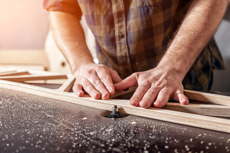 Młody człowiek cieśla budowniczy w odzieży roboczej obrabia drewnianą deskę za pomocą frezarki w warsztacie, wokół dużo sprzętu, drewniane deski. Koncepcje naprawy domu. Zdjęcie Seryjne