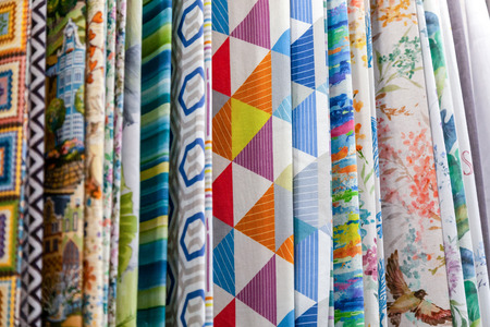 Close-up rows of pieces of fabric made of cotton, polyester, tapestry and other materials of different colors and prints for sewing curtains, bedding and clothing