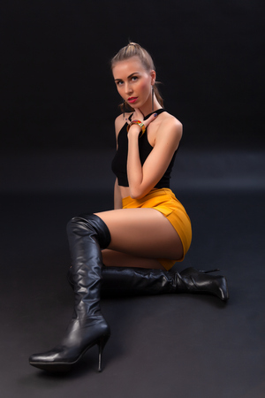Giovane e sorprendente donna bionda con trucco glamour, indossa una giacca di pelle nera, top nero, gonna corta e stivali in posa in studio con sfondo scuro
