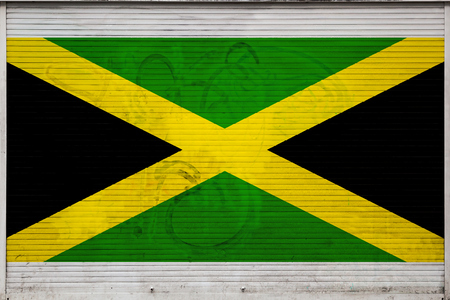 Close-up of old metal wall with national flag of Jamaica. Concept of Jamaica export-import, storage of goods and national delivery of goods. Flag in grunge style