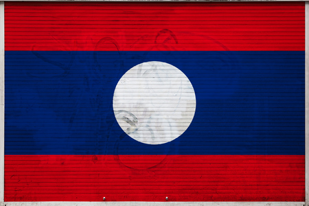 Close-up of old metal wall with national flag of Laos. Concept of Laos export-import, storage of goods and national delivery of goods. Flag in grunge style Standard-Bild