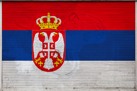 Close-up of old metal wall with national flag of Serbia. Concept of Serbia export-import, storage of goods and national delivery of goods. Flag in grunge style