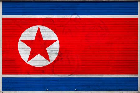 Close-up of old metal wall with national flag of North Korea. Concept of North Korea export-import, storage of goods and national delivery of goods. Flag in grunge style