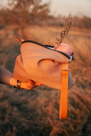 Close-up of a young woman holding a handmade bag with accessories for knitting: knitting needles, crochet hooks, pink ball of yarn, against a background of a field