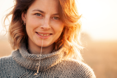 Portrait joyful young woman   brunette in brown knit sweater made of natural wool and jeans holding a spike and smiles mysteriously and enjoy day on field. stylish hipster woman.