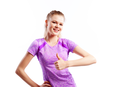 A dark-haired woman coach in a sporty pink short t-shirts and shorts shows thumb up and smiles  on a  white isolated background in studio