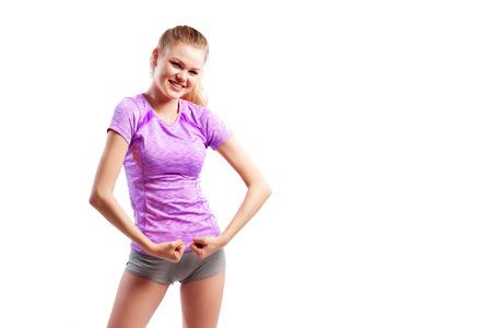 Un entraîneur de femme aux cheveux noirs dans un t-shirt court rose sportif et un short montre des biceps et des sourires sur un fond blanc isolé en studio