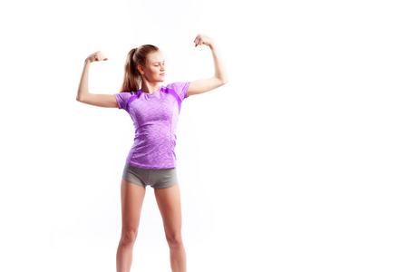 A dark-haired woman coach in a sporty pink short t-shirts and shorts shows biceps and smiles  on a  white isolated background in studio