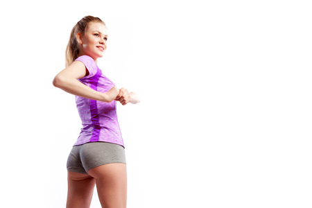 A young  slim woman athlete  in a sporty pink top and shorts makes turns a side and smilling on a  white isolated background in studio, back view. Portrait of a beautiful sportswoman Imagens