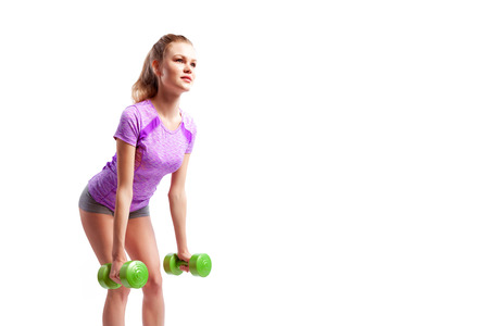 Young woman in sports clothes makes deadlift with weights dumbbell in semi-sitting position on white isolated background. Side view.Fit girl living an active lifestyle