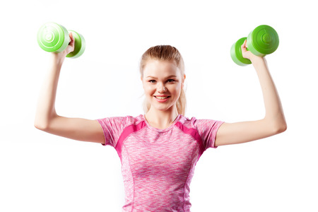 Close up of a Young sportive woman fitness model blonde doing exercise with dumbbell on biceps on white isolated background. Fit girl living an active lifestyle