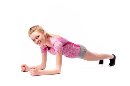 Junge Frau in Sportkleidung lächelt, posiert und steht auf den Armen in der Plankenposition auf dem Boden auf weißem, isoliertem Hintergrund. Seitenansicht. Fit Mädchen, das einen aktiven Lebensstil lebt Standard-Bild