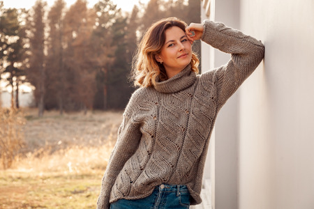 Fashion lifestyle portrait of young trendy woman dressed in brown knit sweater made of natural wool and jeans laughing, smiling, posing and  against a white wall in the street .Portrait of joyful woman