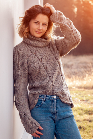 Portrait of a beautiful young model in knitted hat  and warm clothes enjoy day, on background field in  sunny autumn day . Autumn warm photo. Imagens