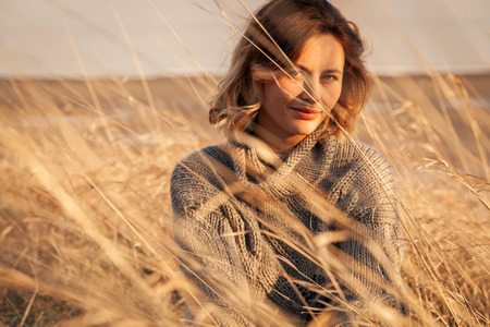 Outdoor close up portrait of young beautiful woman in brown knit sweater made of natural wool and jeans posing on field in autumn park.  Autumn walking concept. Stock Photo