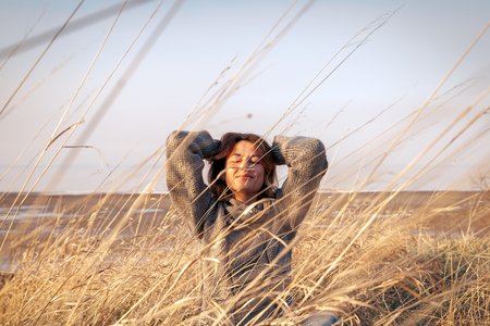 Fashion lifestyle portrait of young trendy woman dressed in brown knit sweater made of natural wool and jeans laughing, smiling, posing and  lies on the field,  view from above .Portrait of joyful woman