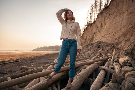 Photo de mode de vie atmosphérique en plein air d'une belle jeune femme aux cheveux noirs, pull en tricot blanc en laine naturelle et jeans sur la plage, en arrière-plan la mer avec le coucher du soleil.