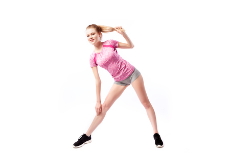 Sporty woman in t-shirt and shorts smilling and tilts to the leg, legs apart shoulder-width apart  on white isolated  background. Photo of muscular woman in sportswear on white background. Strength and motivation. Foto de archivo