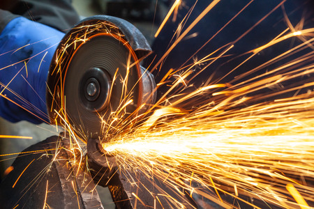 Close-up on the sides fly bright sparks from the angle grinder machine. A young male welder in a white working gloves grinds a metal product with angle grinder in the garage Stock fotó