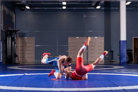 Zwei starke Ringer in blauen und roten Ringerstrumpfhosen ringen und machen einen Hüftwurf auf einem gelben Ringerteppich in der Turnhalle. Junger Mann, der Greifer tut.