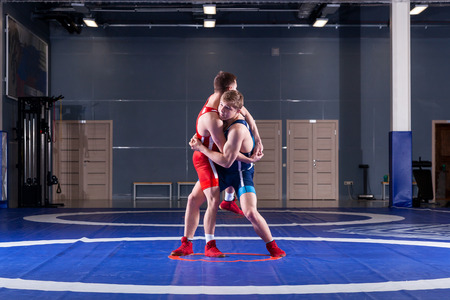 The concept of fair wrestling. Two greco-roman  wrestlers in red and blue uniform wrestling   on a wrestling carpet in the gym