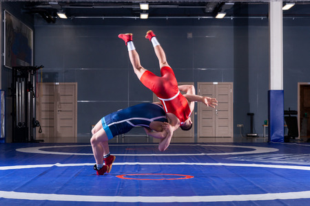 Two young men in blue and red wrestling tights are wrestlng and making a suplex wrestling on a yellow wrestling carpet in the gym. The concept of fair wrestling Stock Photo