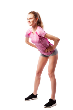 Sport exercises on a white background, fitness concept. Young woman in comfortable sportswear (shorts and top) smiles charmingly and bends forward on white isolated background