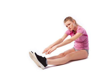 Sport exercises on a white background, fitness concept. Young woman in comfortable sportswear (shorts and top) is tired and bends forward to her legs, stretches on a white isolated background 스톡 콘텐츠