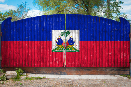 Close-up of the national flag of Haiti on a wooden gate at the entrance to the closed territory on a summer day. The concept of storage of goods, entry to a closed area, tourism in Haiti