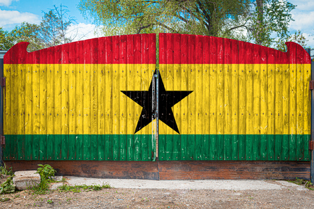 Close-up of the national flag of Ghana on a wooden gate at the entrance to the closed territory on a summer day. The concept of storage of goods, entry to a closed area, tourism in Ghana