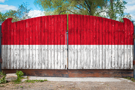 Close-up of the national flag of Indonesia on a wooden gate at the entrance to the closed territory on a summer day. The concept of storage of goods, entry to a closed area, tourism in Indonesia