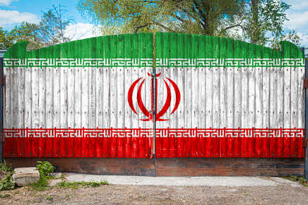 Close-up of the national flag of Iran on a wooden gate at the entrance to the closed territory on a summer day. The concept of storage of goods, entry to a closed area, tourism in Iran Stock Photo