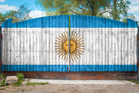 Close-up of the national flag of Argentina on a wooden gate at the entrance to the closed territory on a summer day. The concept of storage of goods, entry to a closed area, tourism in Argentina