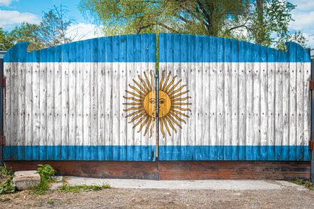 Nahaufnahme der Nationalflagge Argentiniens auf einem Holztor am Eingang zum geschlossenen Gebiet an einem Sommertag. Das Konzept der Warenlagerung, Eintritt in ein geschlossenes Gebiet, Tourismus in Argentinien